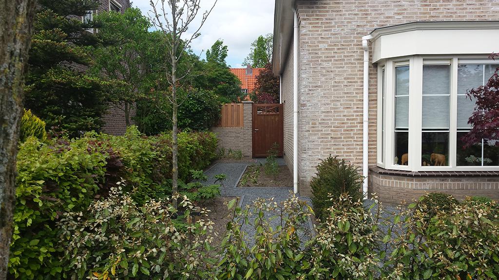 Pad met poort langs huis JVM Tuinen